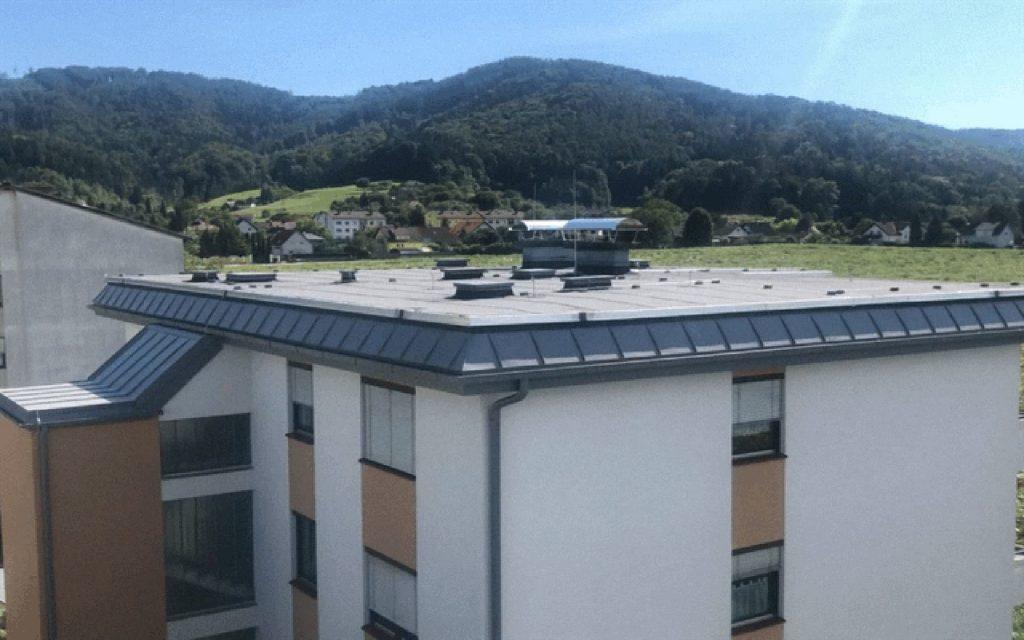 Ansicht von einem Bitumen-Flachdach mit Fassadenverblechung-Stehfalz-System, ausgeführt in Gratwein-Straßengel